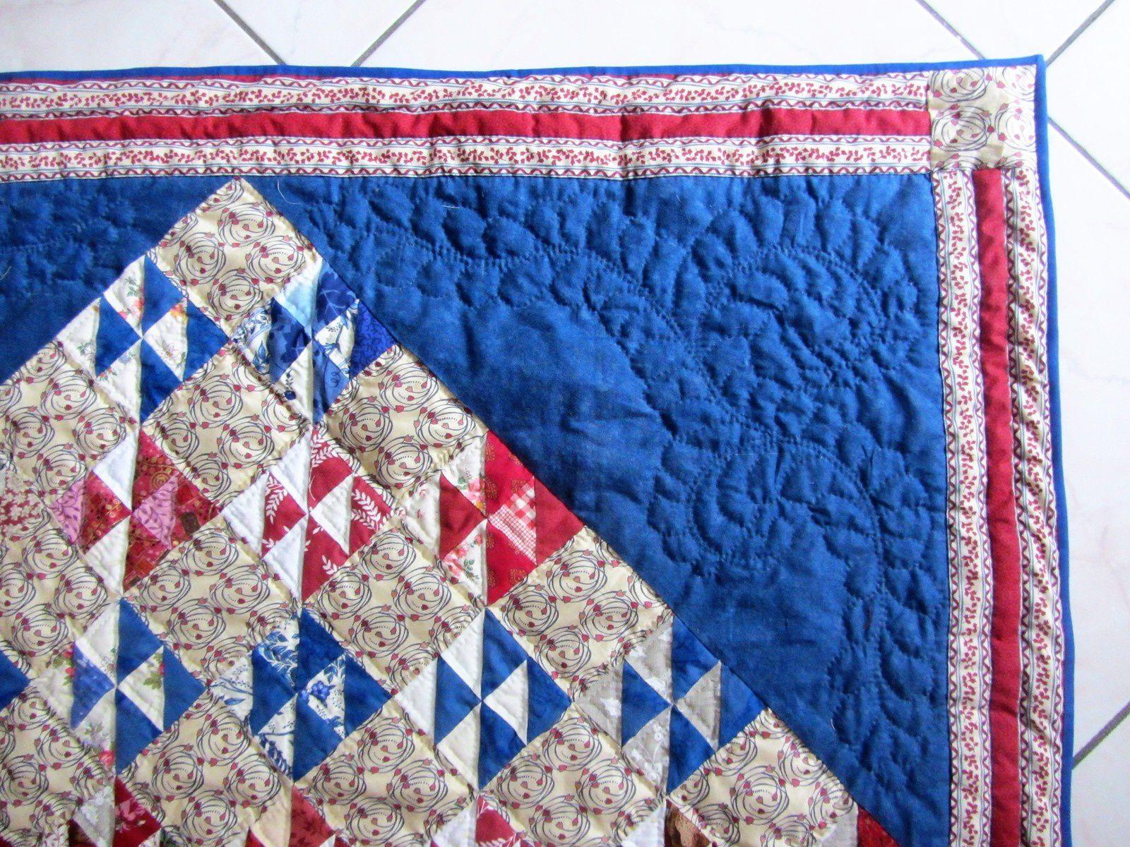 Réalisé avec du tissu liberty pour les carrés intermédiaires. Et un très joli quilting pour les angles.