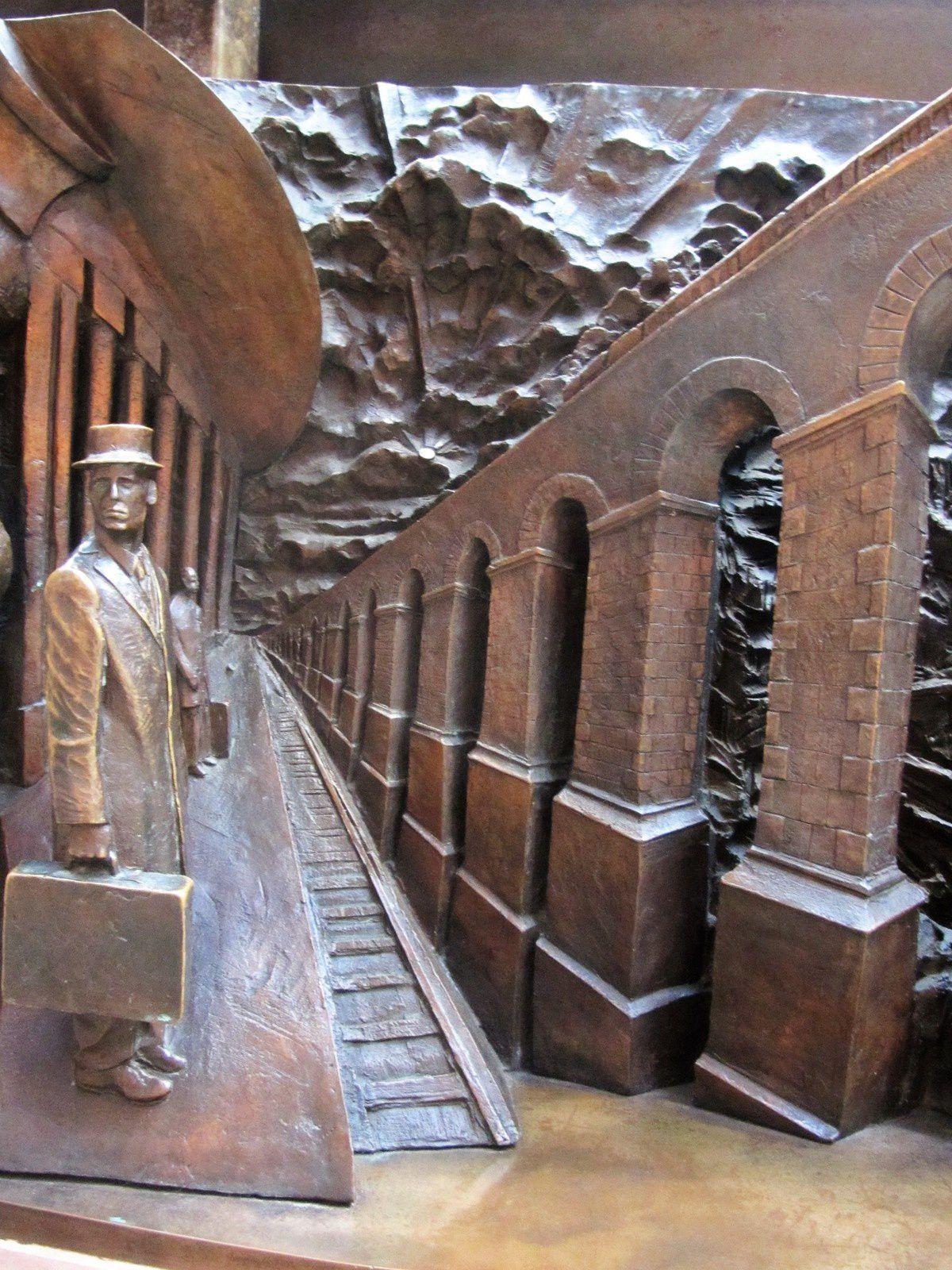 """Sur le socle de la statue """"rendez-vous"""" de Paul Day, il y a quelques évocations de voyage en train."""