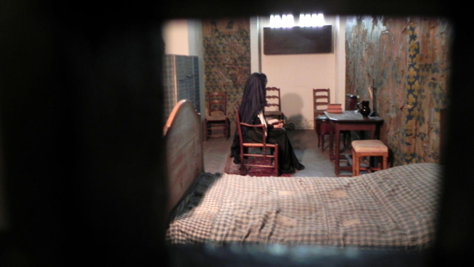 La cellule de Marie Antoinette vue par une ouverture dans une porte sur le côté.