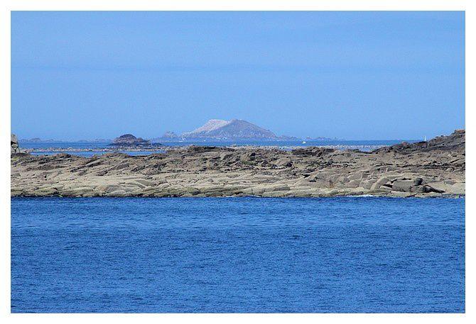 au fond l'île Rouzic, la partie plus au nord semble être de calcaire (blanche), en fait ce sont les fous de Bassan qui donnent cette couleur blanche tant ils sont nombreux.
