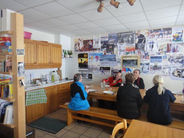Le mur est recouvert d'affiches ou de dossards de courses de ski régionales.
