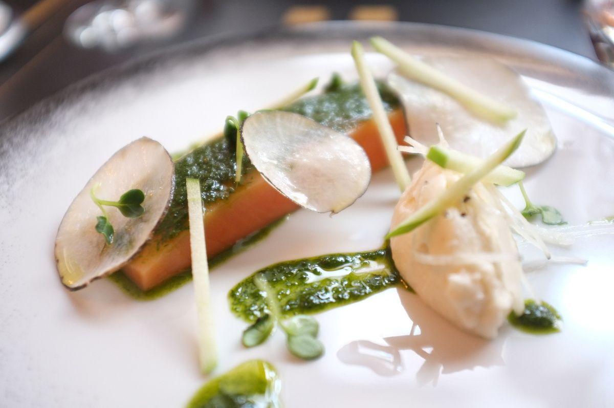 Une assiette blanche avec du poisson orange, des bouts de légumes et du caca de Shrek très bon