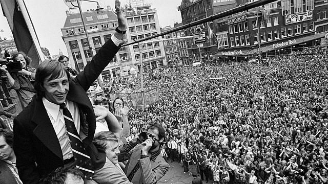 Cruyff saluant la foule à Amsterdam, en 1974. Par Nationaal Archief — Huldiging op Leidseplein in Amsterdam &#x3B; Cruyff wordt toegejuichdCollection / Archief : Fotocollectie AnefoNummer toegang : 2.24.01.05Filenumber : 927-3143, CC BY-SA 3.0 nl