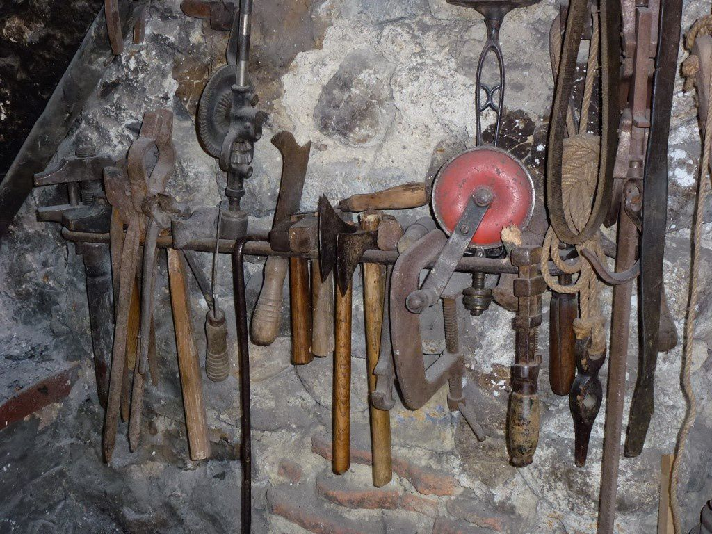 Près du foyer, on distingue très bien à gauche les tenailles de forge au milieu d'autres outils...
