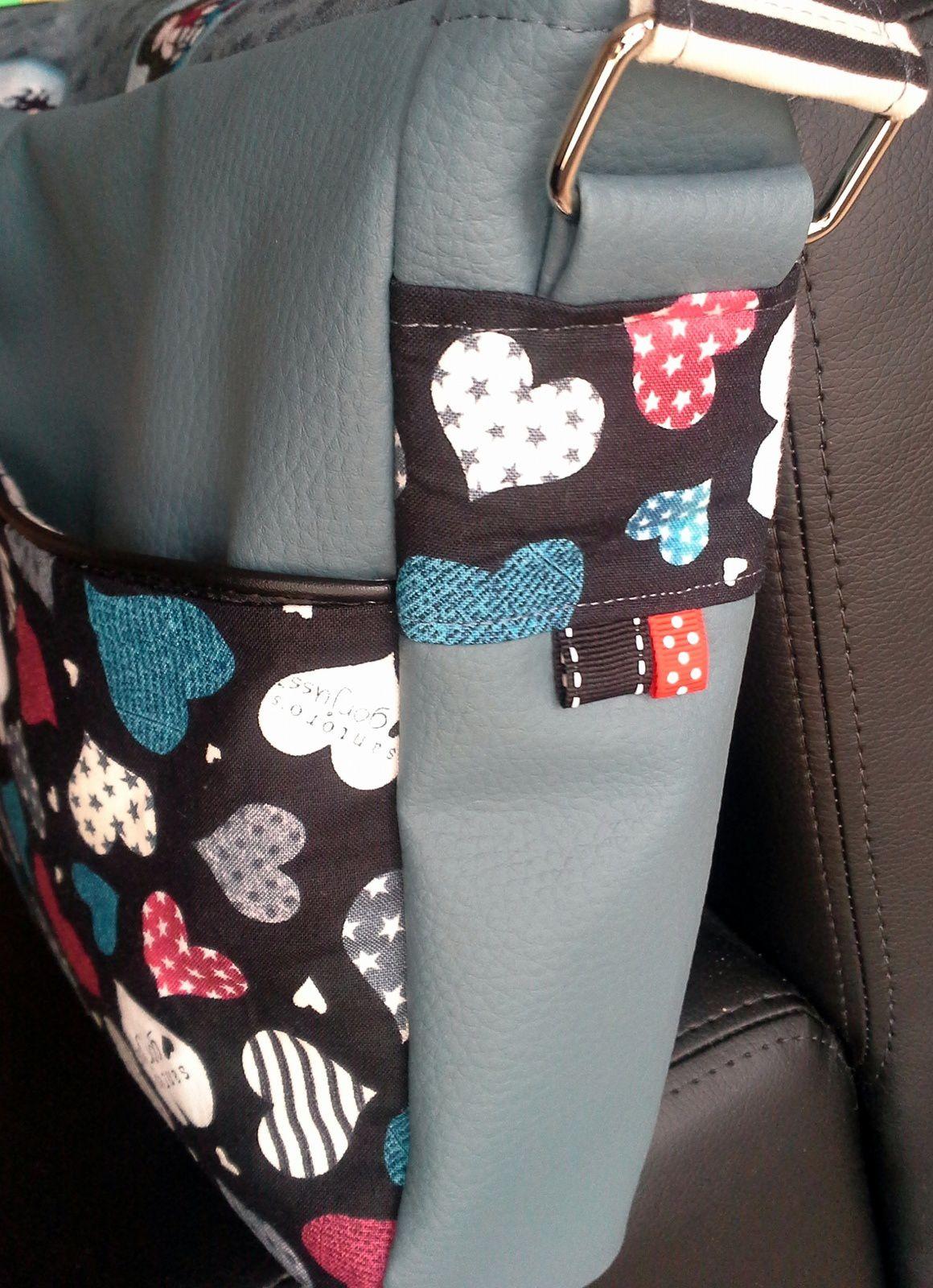 J'ai ajouté une poche au dos, des décos sur les cotés, et du passepoil (rabat plus poche devant) par rapport au modèle original