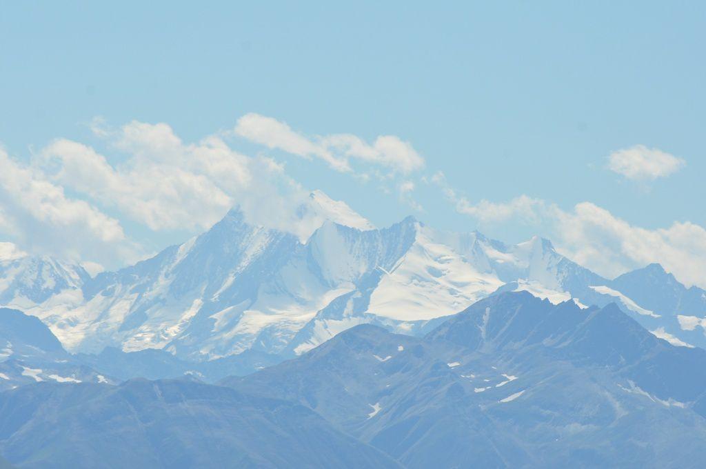 Un couvre-chef bien connu à côté d'un petit cairn et dans le lointain les 4000 m enneigés.