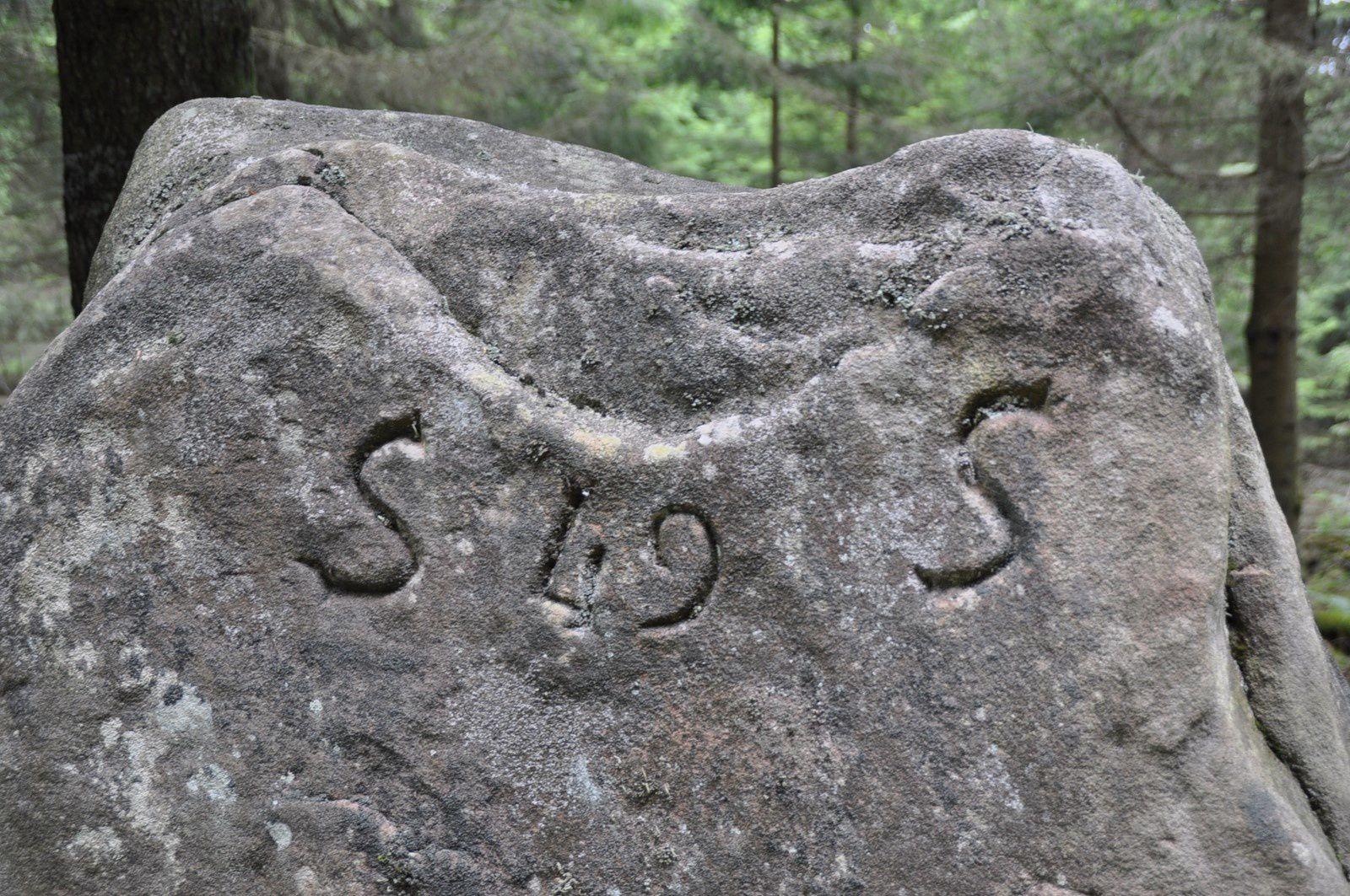 Pierre levée avec des inscriptions, situé dans une limite de département