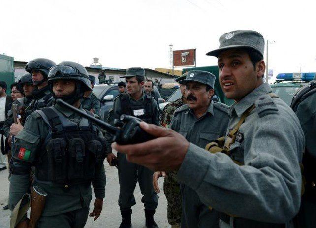Les forces de sécurité afghanes devant le siège de la Commission électorale indépendante cible d'une attaque des talibans le 29 mars 2014 à Kaboul (Wakil Kohsar/AFP)
