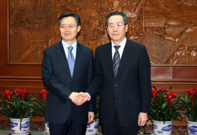 South Korea's nuclear envoy Hwang Joon-kook shakes hands with his Chinese counterpart Wu Dawei on April 11 after a meeting to exchange views on the threat of another North Korean nuclear test. (Yonhap)