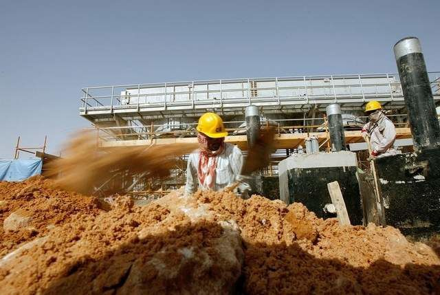 Laborers help build an oil processing facility in 2008 for Saudi Aramco, one of the companies attacked by Iranian hackers, according to a new report.