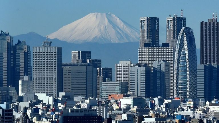 Japan's highest mountain, Mount Fuji (C) is seen behind the skyline of the Shinjuku area of Tokyo. (AFP/KAZUHIRO NOGI)