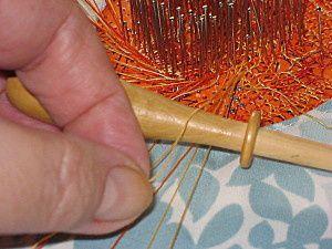 Glisser le deuxième fuseau de la paire à travers la boucle et remettre l'épingle.