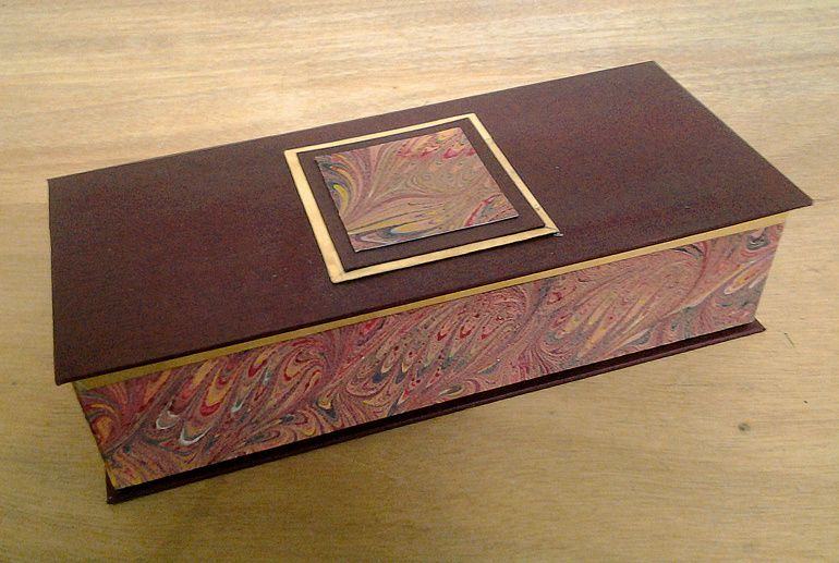 Coffret à montres gainé de simili cuir, papier reliure à la cuve et feuille d'or.  Réalisé par Dominique N.