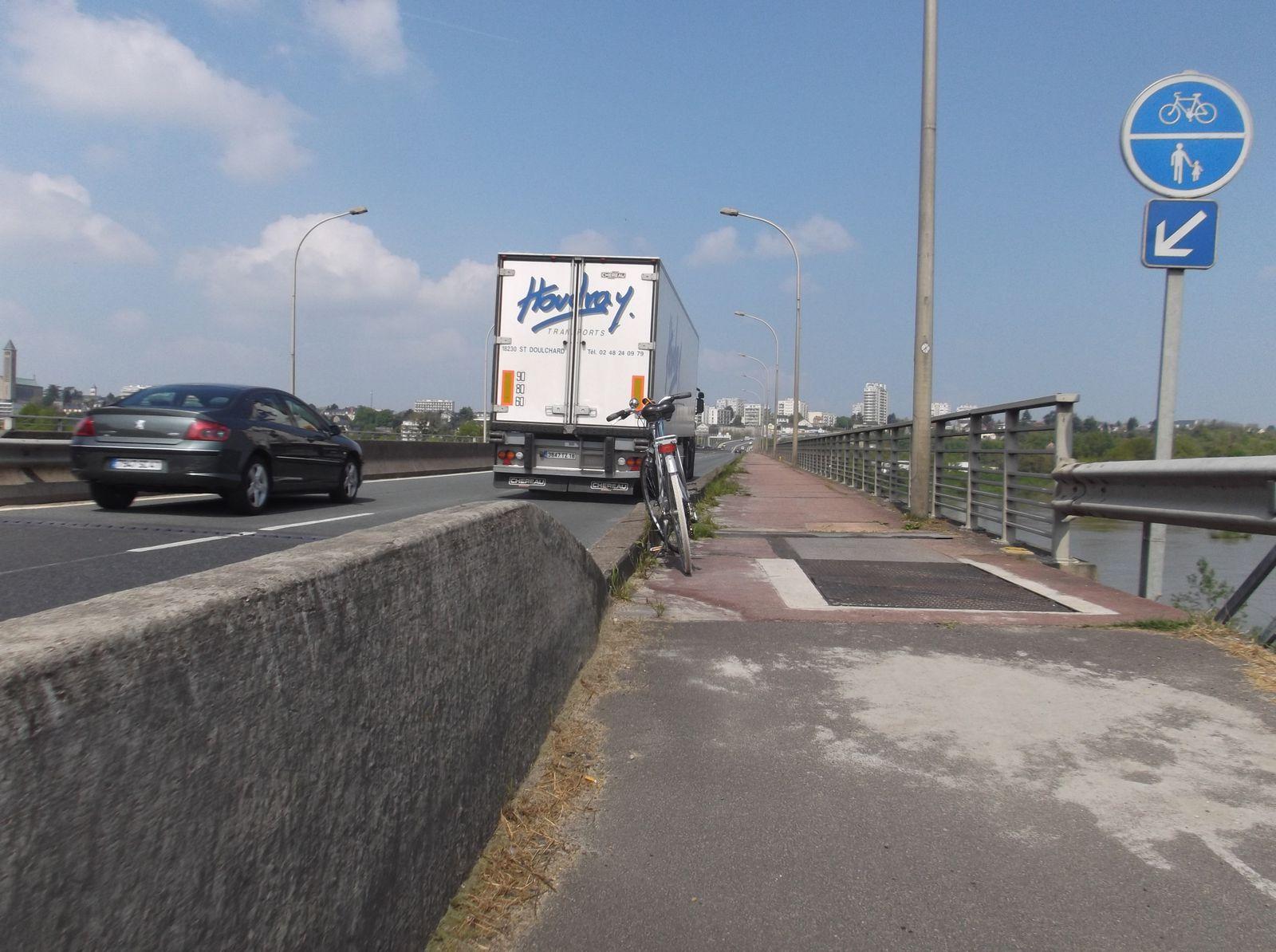 """Sans doute le plus périlleux: (D174 ) Sur le pont Charles De Gaulle rive gauche en venant de Vineuil sur le trottoir un panneau rond bleu avec côte à côte les logos piétons et vélo. Ce panneau ne semble pas avoir d'existence légale. Proposition d'aménagement d'une séparation entre route et """"voie verte"""" sous forme d'un écran, protégeant des chutes sur chaussée, du bruit et des vents dominants (sud-ouest) ."""