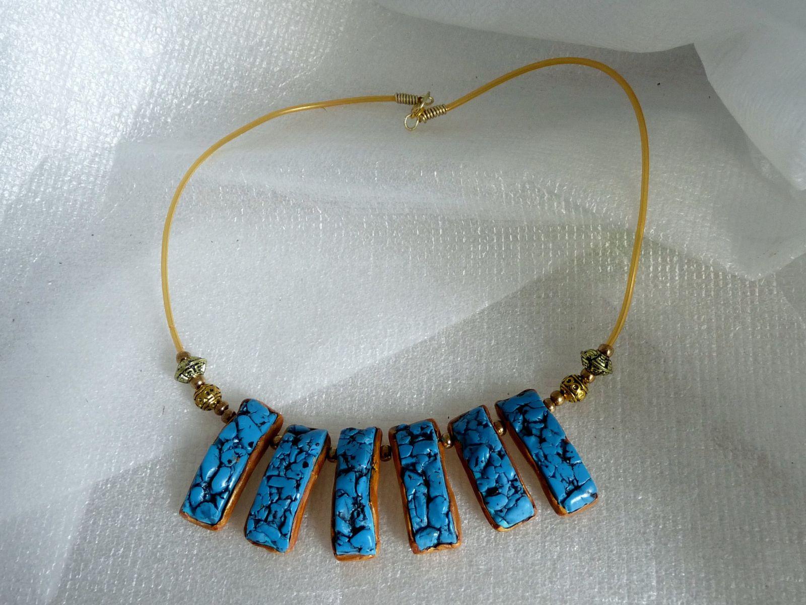 Un collier bâtonnets légèrement incurvés assortis de perles métal vieil or