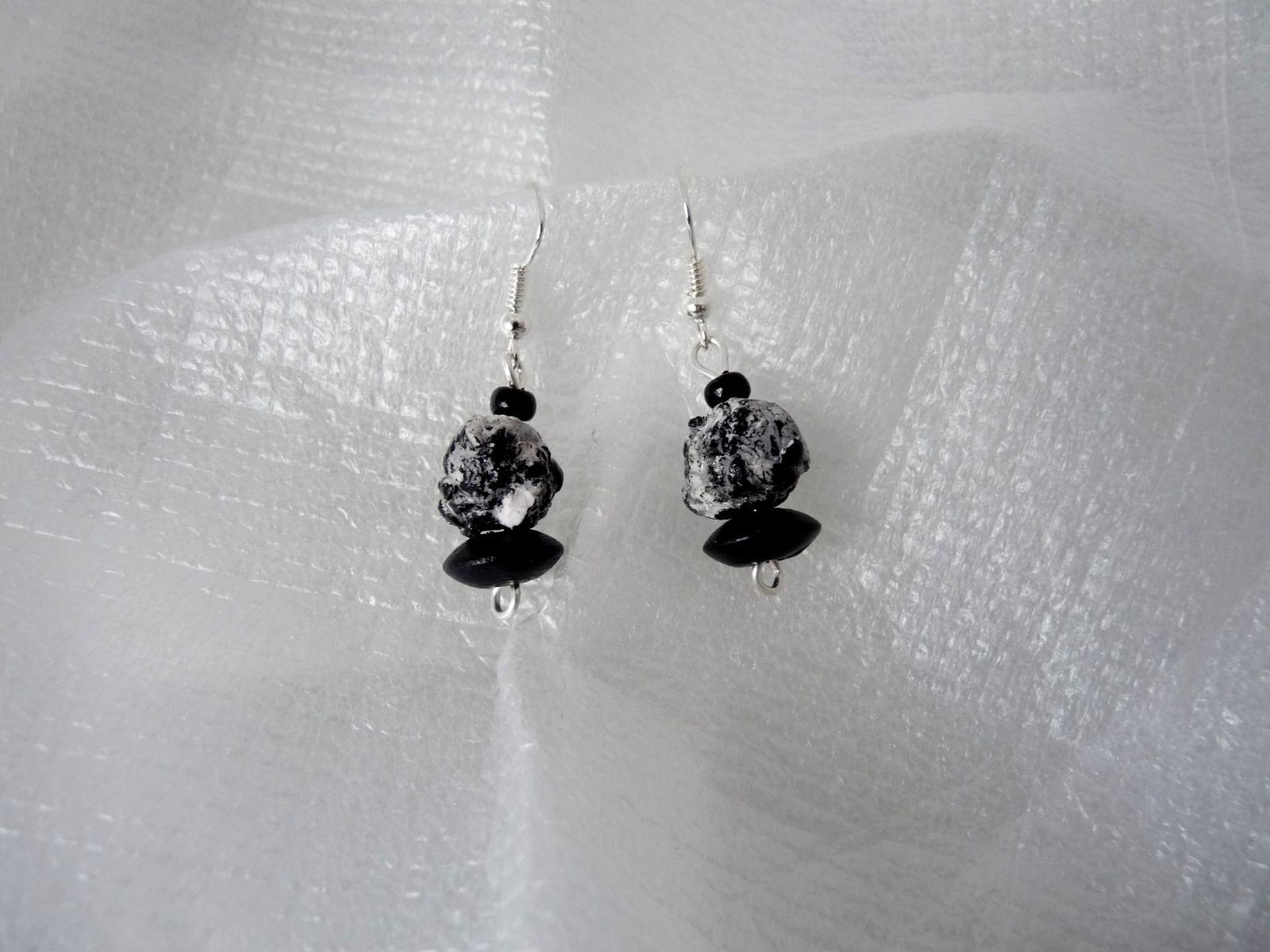 Un collier de perles craquelées inégales partinées à l'acrylique noire accompagnées de quelques perles en bois avec toujours les boucles d'oreille assorties