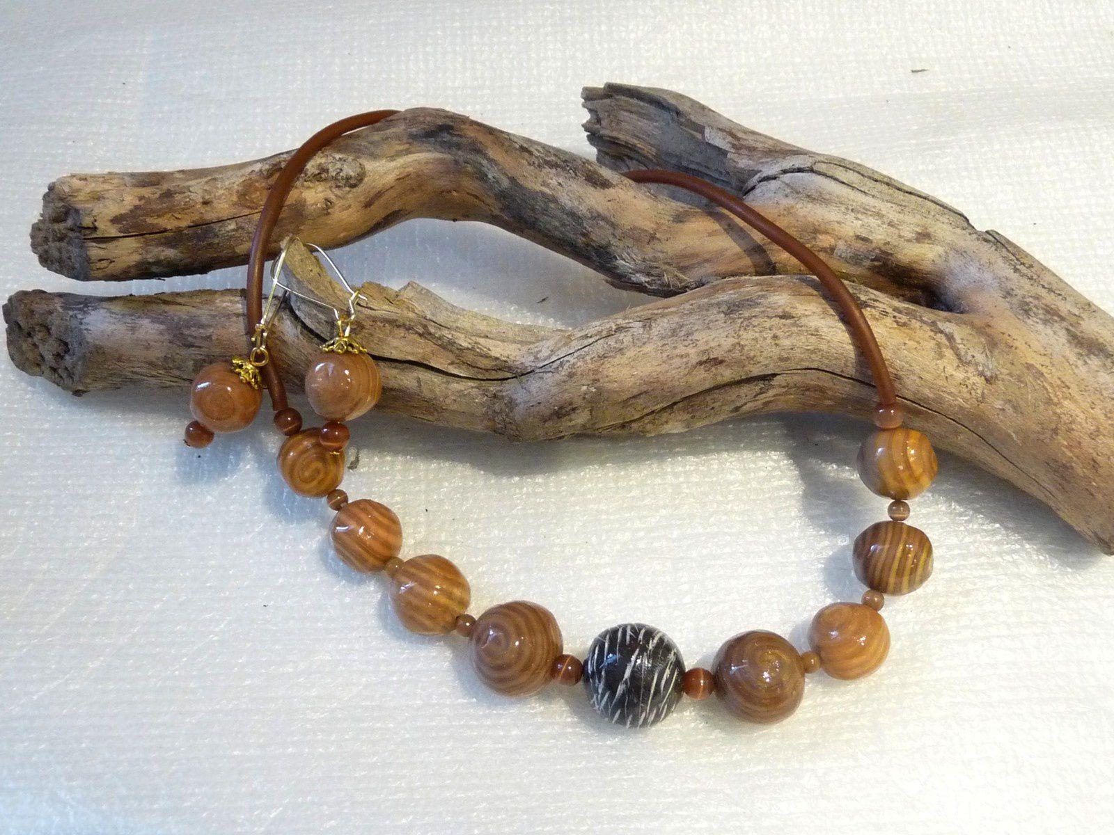 Un collier de perles rondes vortex avec une perles centrale marron structurée et patinée assorti d'une paire de boucles d'oreille perles rondes montées chacune sur une grande dormeuse dorée