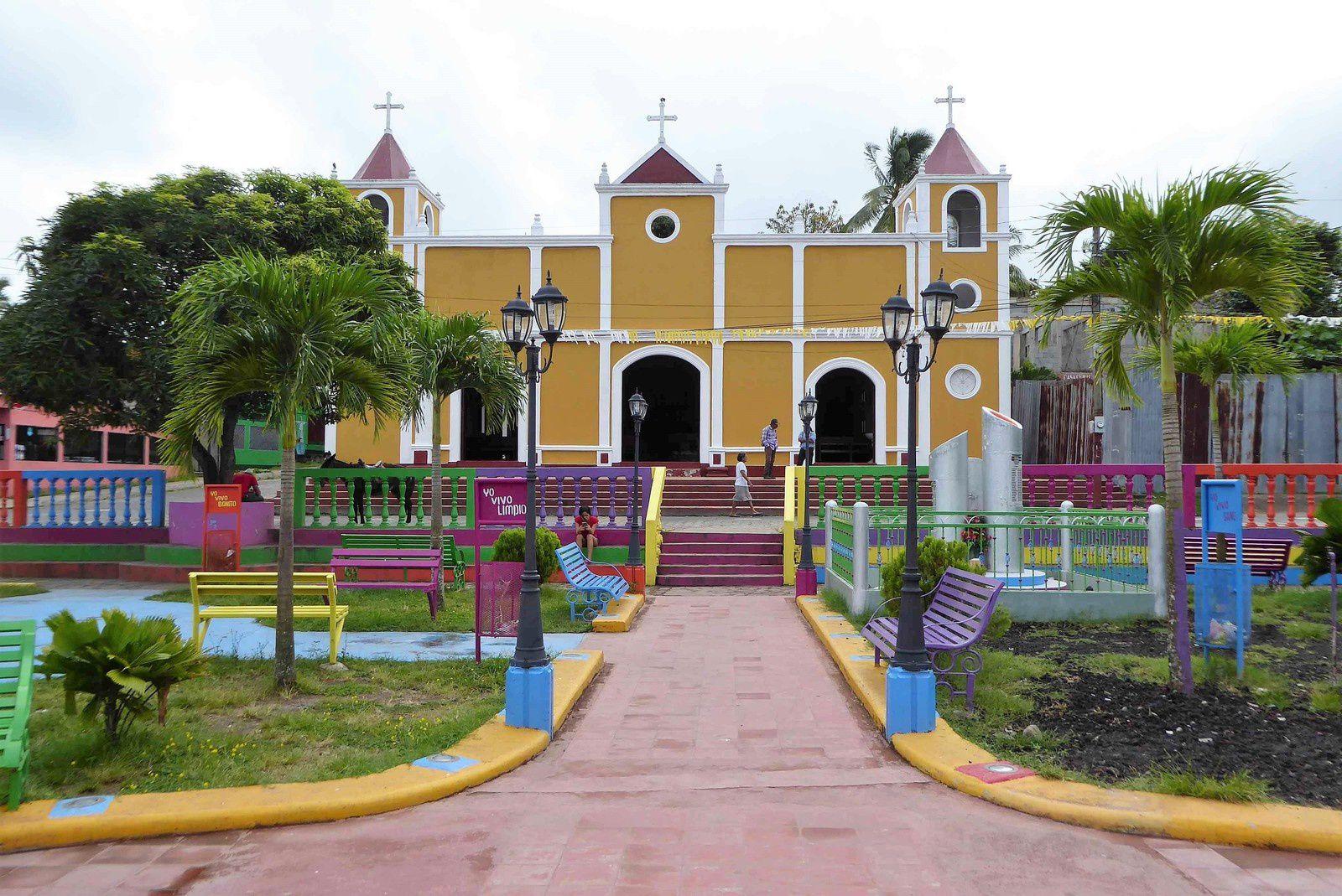 L'église avec en premier plan le parc de jeux et aussi le monument aux morts (les 3 cylindres devant l'angle droit de l'église) avec la liste des morts qui marque un lourd tribut du village lors de la guerre des années 1990