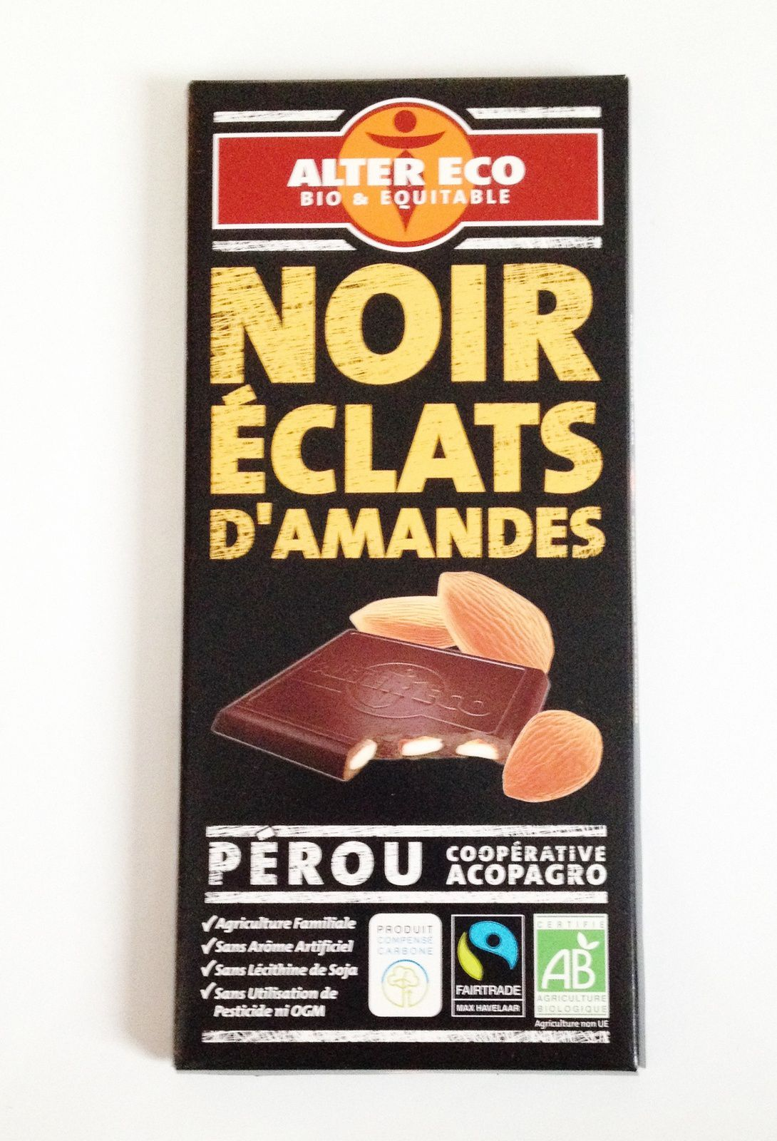 Du chocolat noir éclats d'amandes provenant du commerce équitable. Rien qu'avec la composition des ingrédients c'est une invitation au voyage: pâte de cacao (Pérou), sucre de canne (Paraguay), beurre de cacao (République Dominicaine), gousses de vanille (Madagascar)