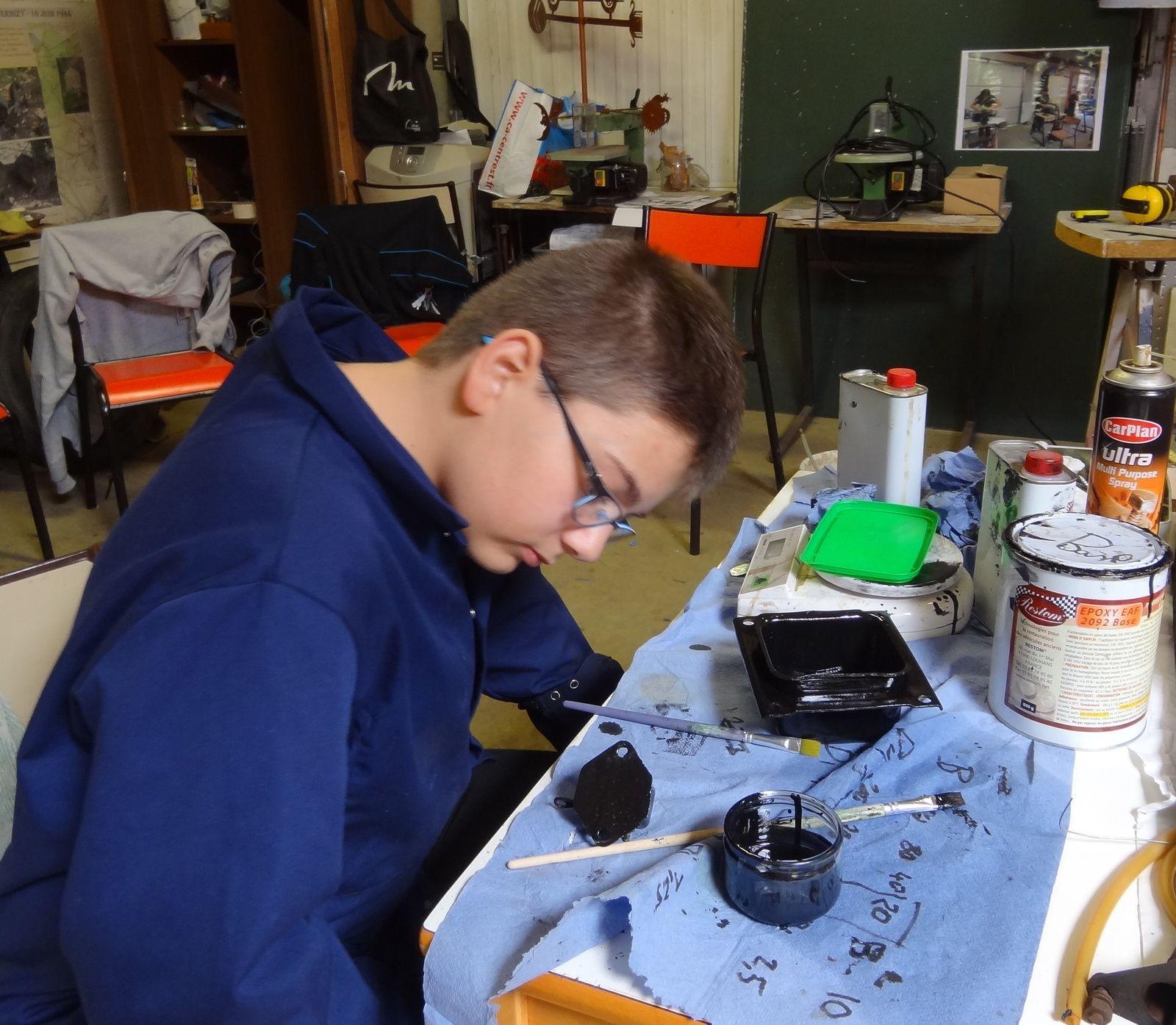 Alexis visualise son travail. Il a peint en particulier en noir le boitier de support du silentbloc arrière du moteur.
