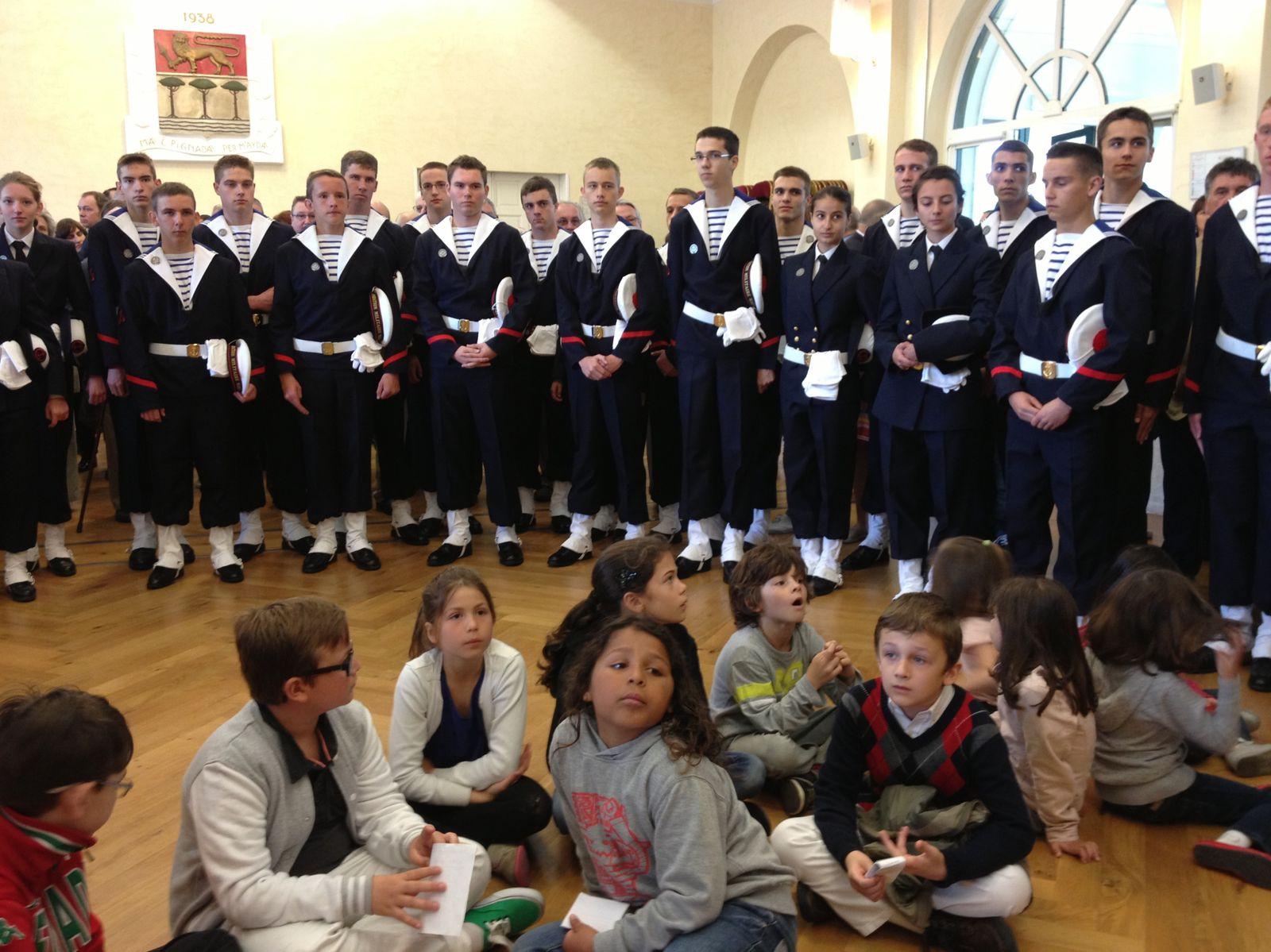 les élèves des écoles et les jeunes de la préparation militaire marine qui viennent d'être honorés écoutent le discours du Maire