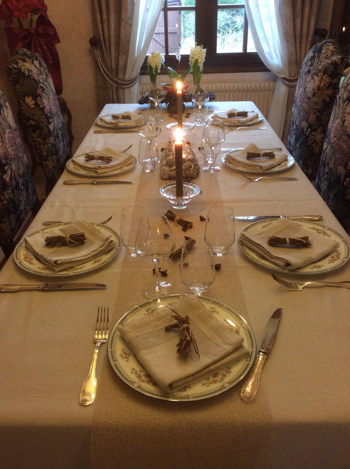 Chemin de table dans les tons de la nappe, centre de table formé de pommes de pin et de photophores