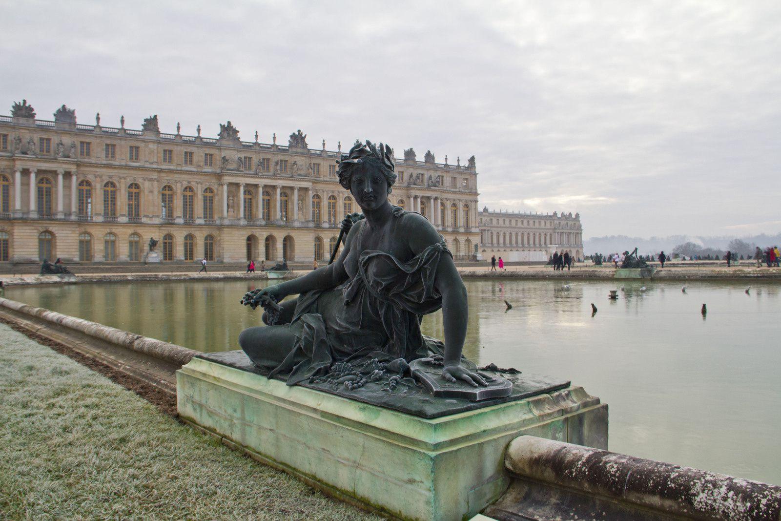 Statues givrées à côté des parterres d'eau et château