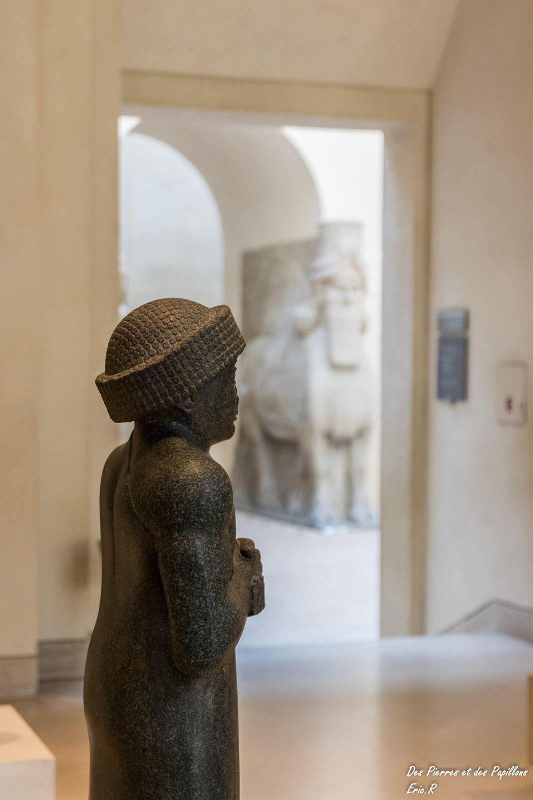 Une statue de Gudea avec en arrière plan les taureaux ailés.