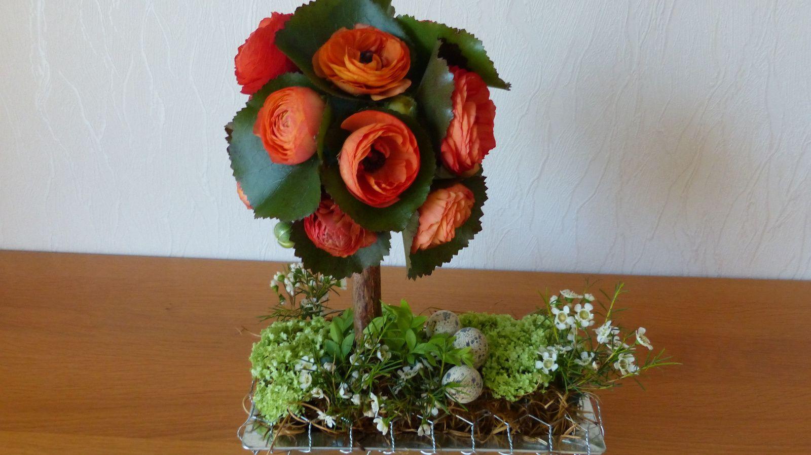 Bouquet du 16 avril : une belle présentation pour accueillir les oeufs de Pâques. Le petit arbre est fait avec des renoncules orange et des feuilles de galax et le reste du décor avec du viburnum et du waxflower ofir.