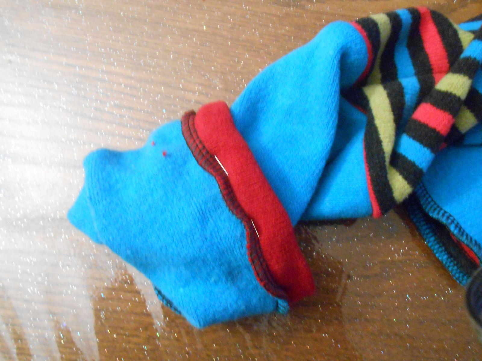 Coudre la bande, l'envers de cette bande contre l'endroit du tissu. Déplier le tout et plier en deux (comme sur ma photo avec les aiguilles). Coudre ensuite au niveau de ces aiguilles, à ras de la couture des deux tissus. La dernière photo montre l'envers du vêtement avant couture.