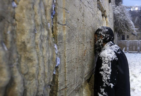 An Ultra-Orthodox Jewish man prays at the Western Wall in Jerusalem's Old City during a snowstorm on 13 December 2013, Reuters/Darren Whiteside