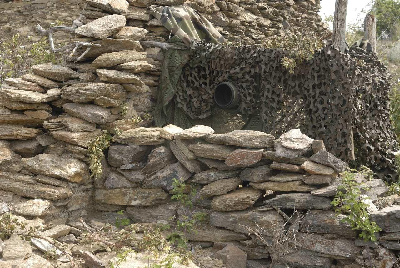 Affût avec des pierres trouvées sur le site et filets de camouflage pour photographier des craves à bec rouge.