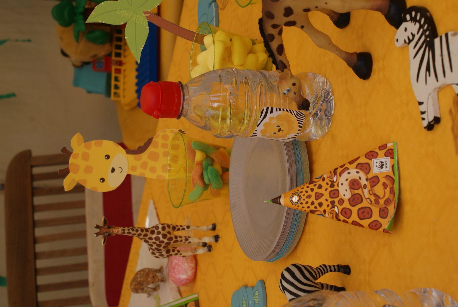 bouteille d eau avec une vignette scotché dessus chaques enfants à choisi son animal et avait sa bouteille perso. En premier plan compote en forme de berlingot décoré animaux savane