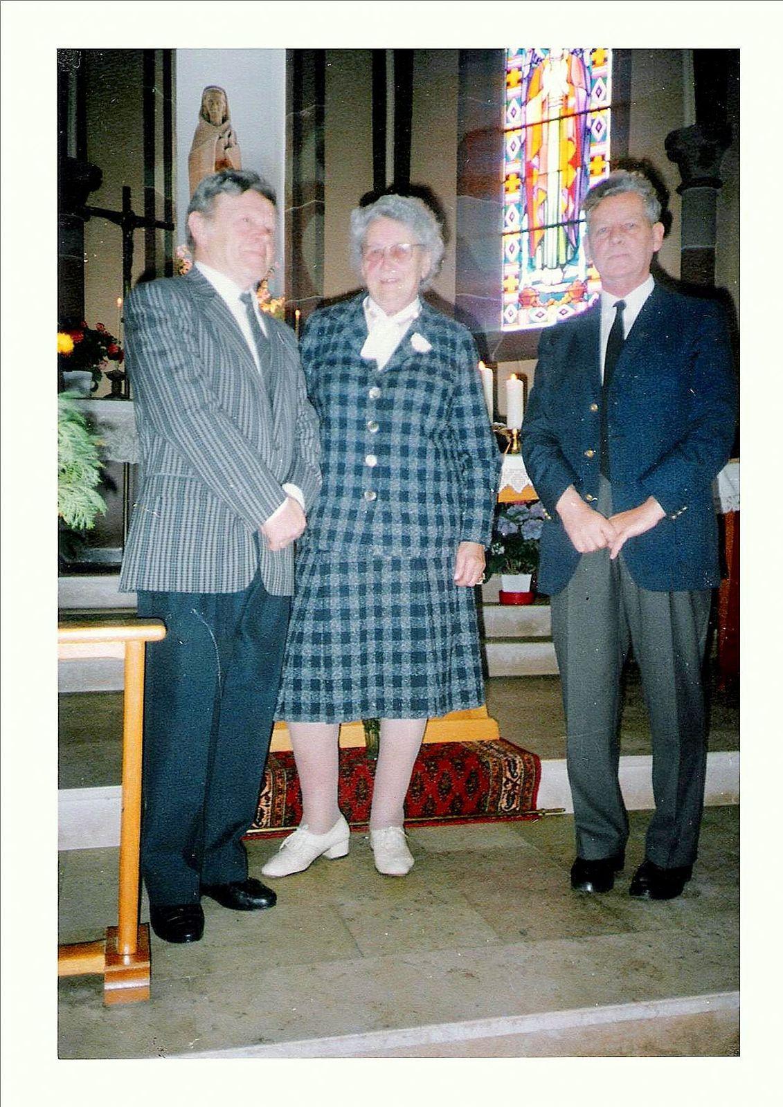 Raymond FUCHS (à gauche) et le Père LUTZ entourant Mme Cécile OLLAND, en 1985