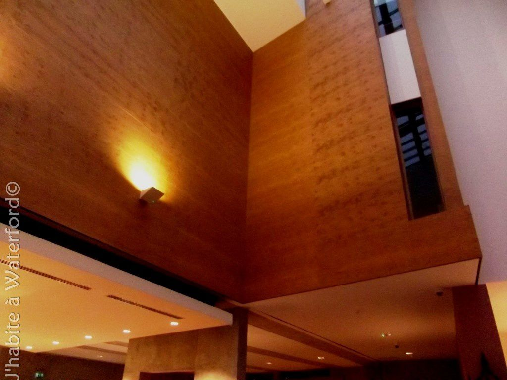 Dans le hall de réception, des panneaux en chêne jusqu'au plafond partiellement vitré qui permet à la lumière du jour de passer. C'est un point où musée, théâtre et mairie ont des murs comuns.