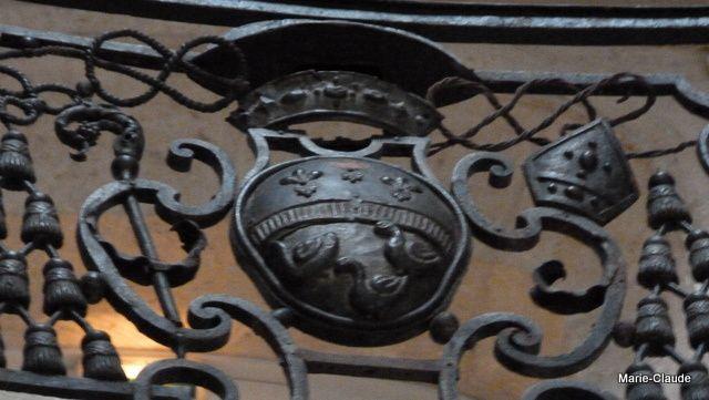 Le blason de l'abbaye en fer forgé sur la rambarde de l'escalier,