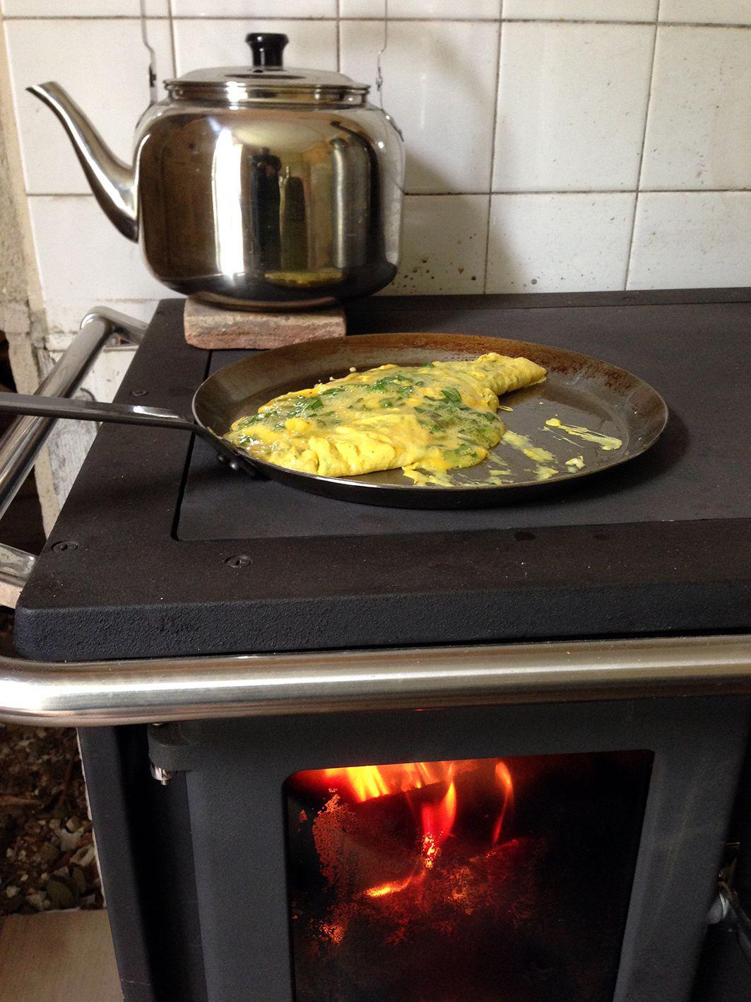 Une omelette (aux herbes du jardin) en premier plan et une bouilloire (6 litres) au second plan.
