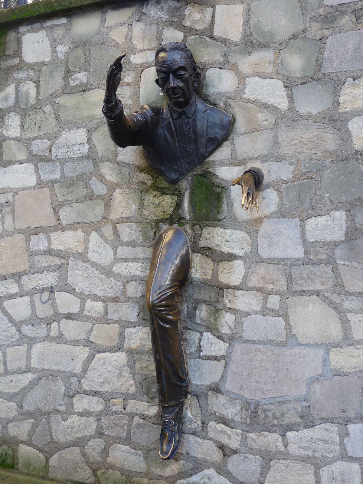 """on arrive rue Norvins au nr 26  habita Marcel Aymé, une sculpture  réalisée par Jean Marais évoquant le"""" Passe-Muraille """""""