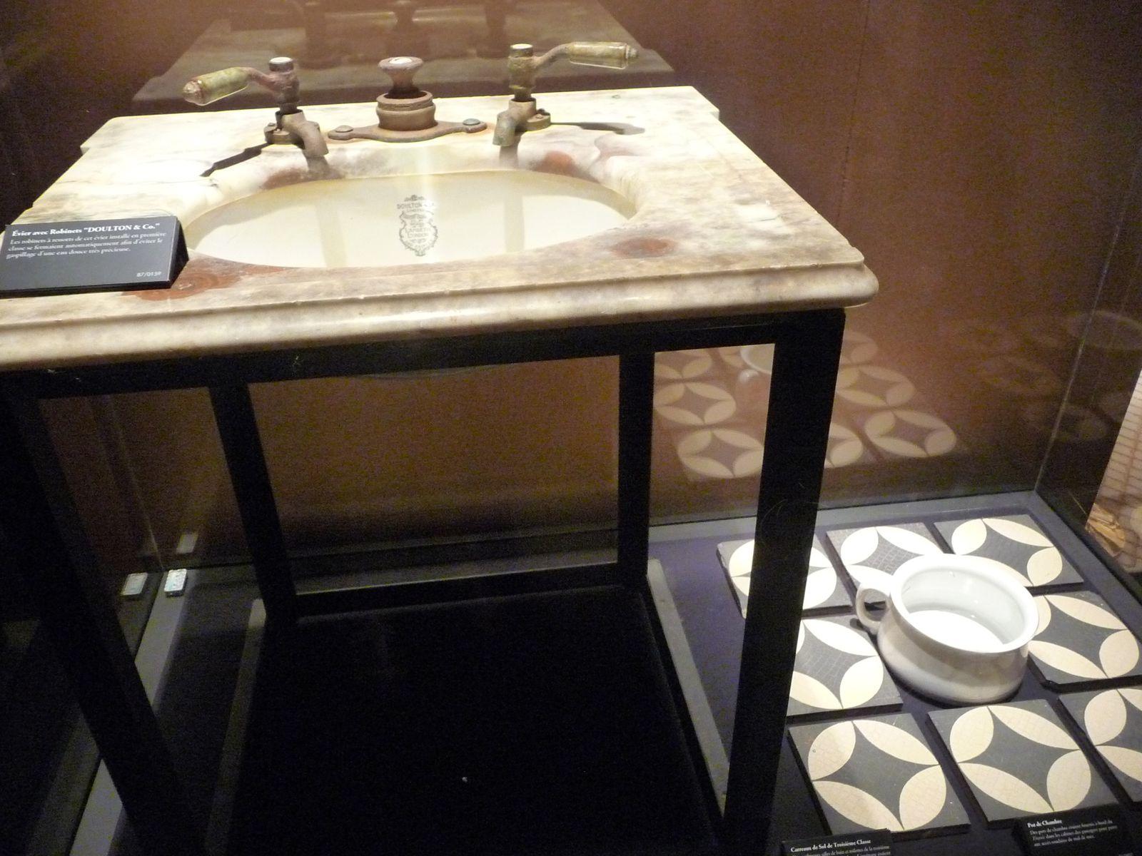 reconstitution d une cabine 1ère classe,   en vitrines les divers objets repêchés  lavabo en marbre  , robinet d ' eau chaude et froide ,  pot de dentrifrice