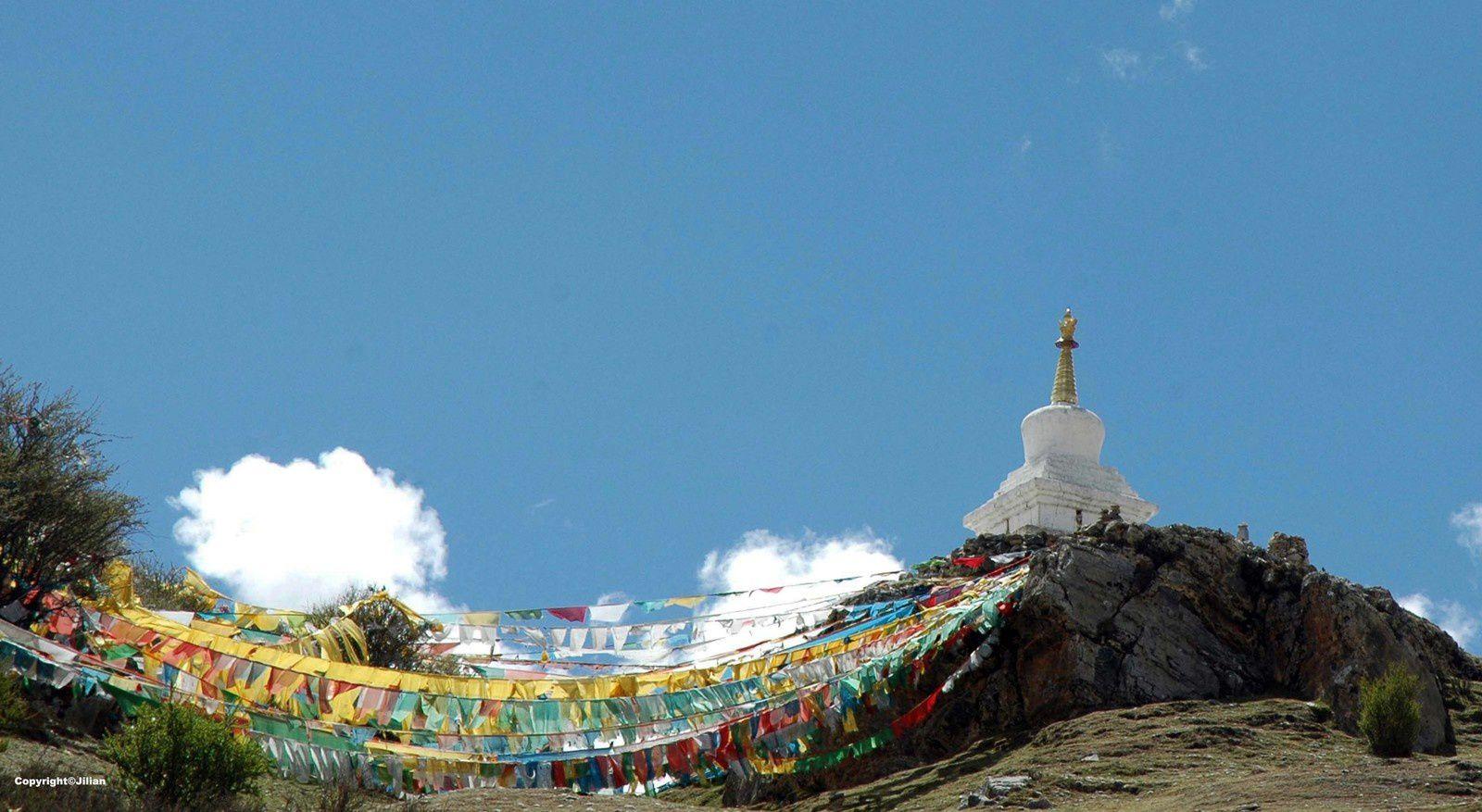 Drapeaux de prières et chorten  (ou stupa, qui contient des reliques d'un important personnage religieux)