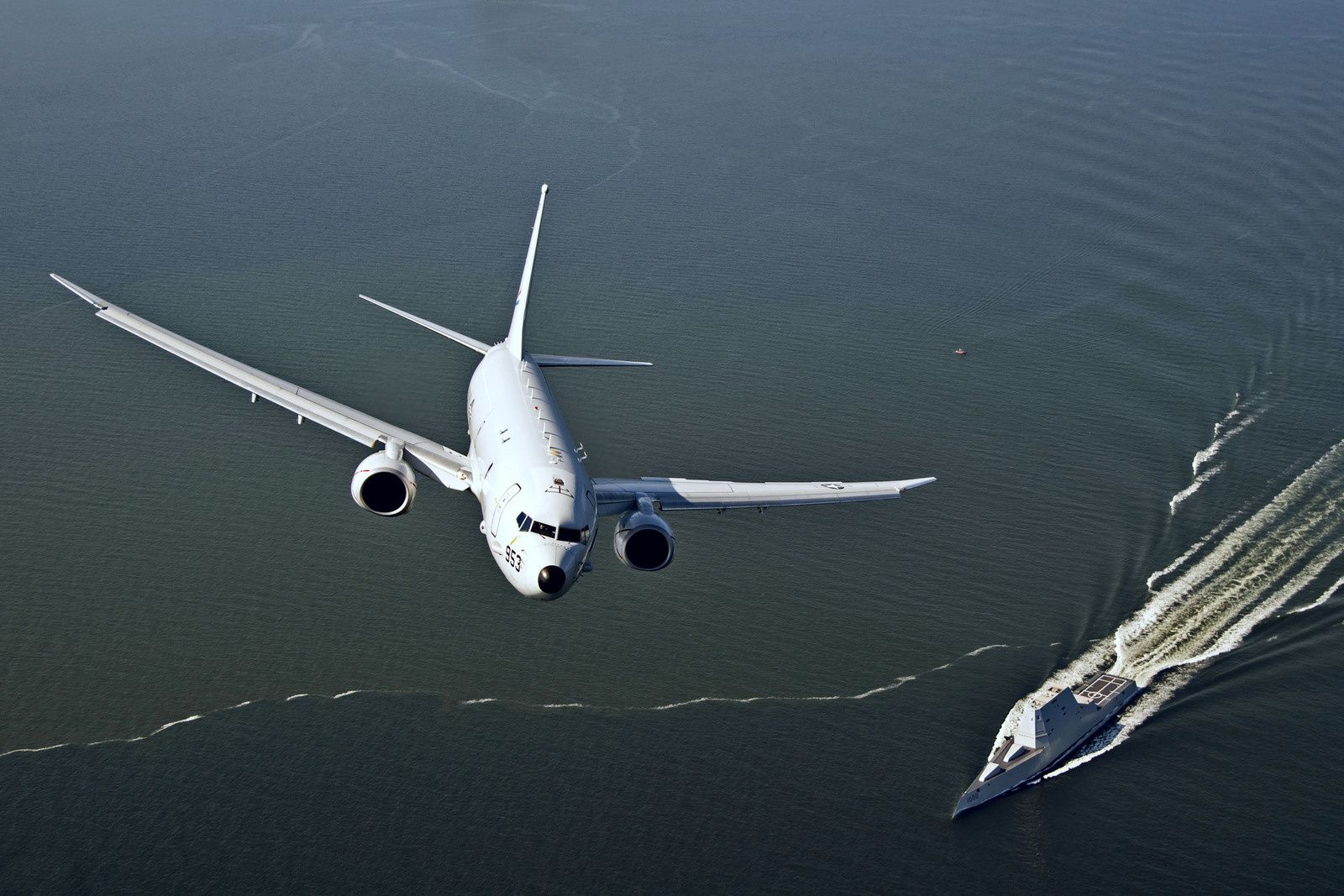 © US Navy - Un P-8A Poseidon de l'Air Test and Evaluation Squadron vole au-dessus de l'USS Zumwalt.
