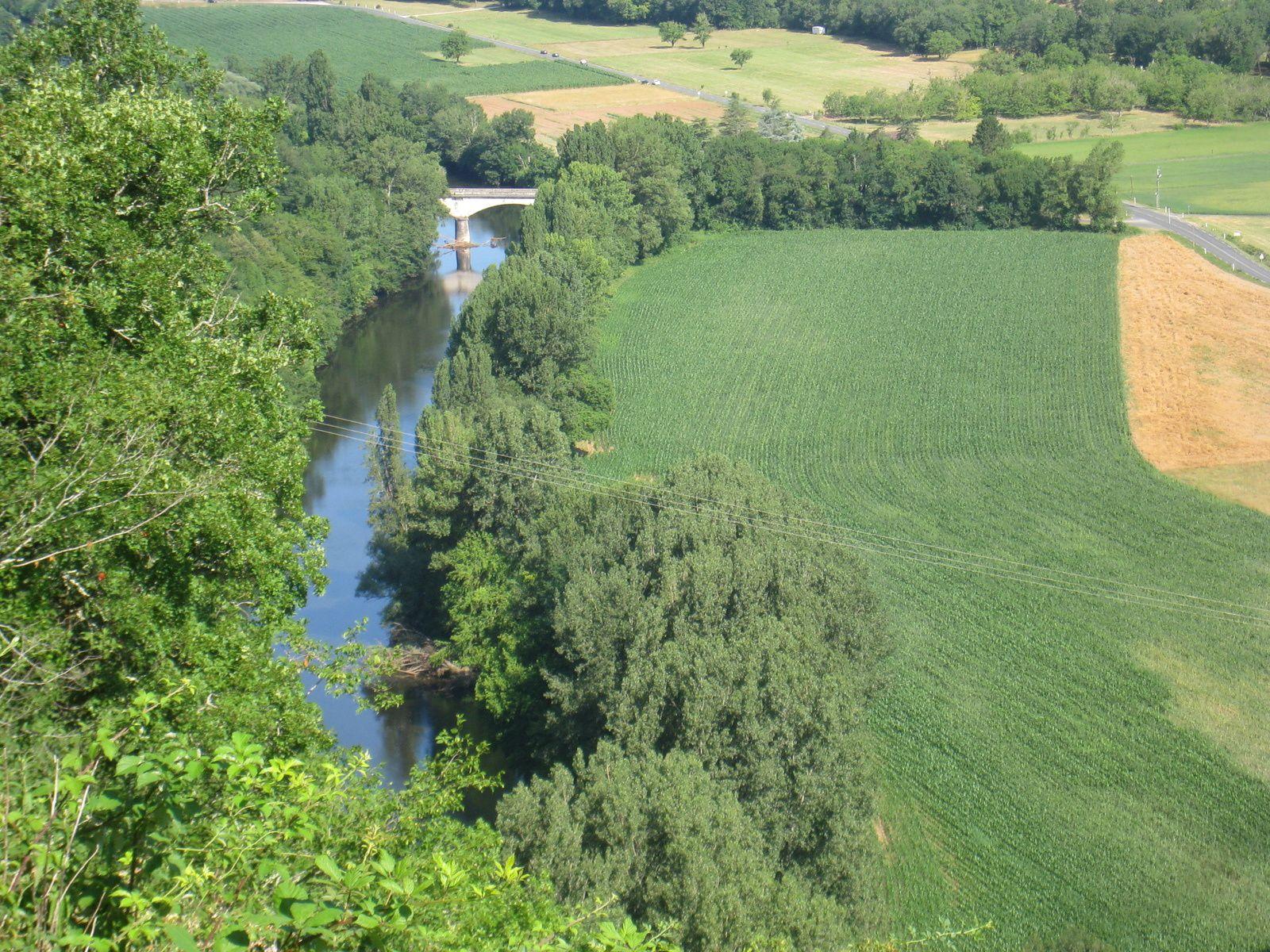 On domine un pont sur la Vézere.qui serpente entre champs de maïs, céréales et noyers.