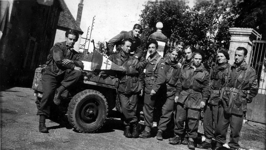 "Belle photo de l'ensemble des SAS formant le peloton SIMON (Lt Simon au centre de la photo) avec la jeep ""IN CHALLAH"" jeep d'Alexis Le Noac'h que l'on voit au fond à moitié caché sur cette photo."