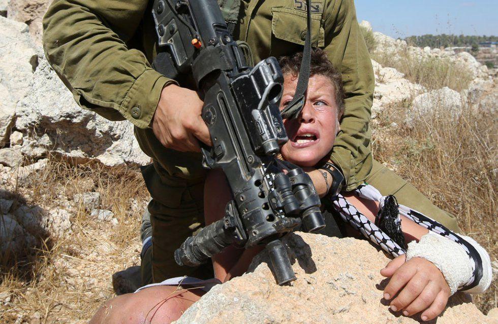 Un soldat israélien tente d'arrêter un enfant palestinien pendant des affrontements à Nabi Saleh, en Cisjordanie, le 28 août 2015.