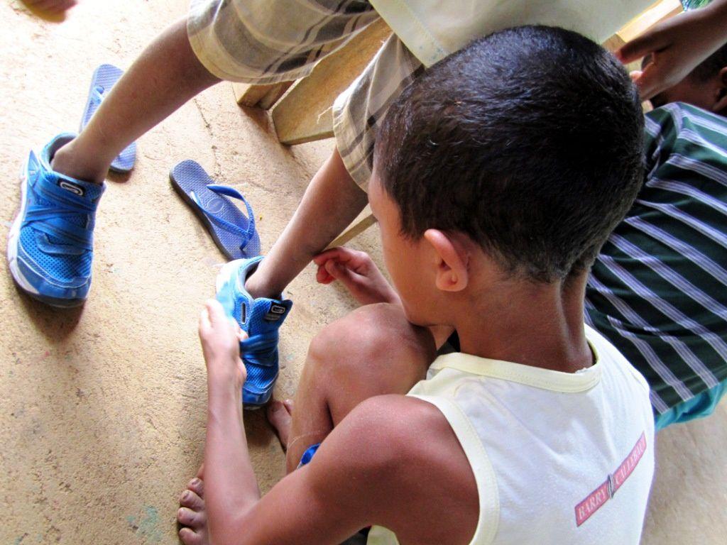 Les enfants s'entraident. Ici, un jeune aide son ami à attacher ses nouvelles chaussures, lui qui passe le plus clair de son temps pieds nus dans la terre et les cailloux de sa fazenda va pouvoir courir sans risque de se blesser, et sa plaie de s'infecter.
