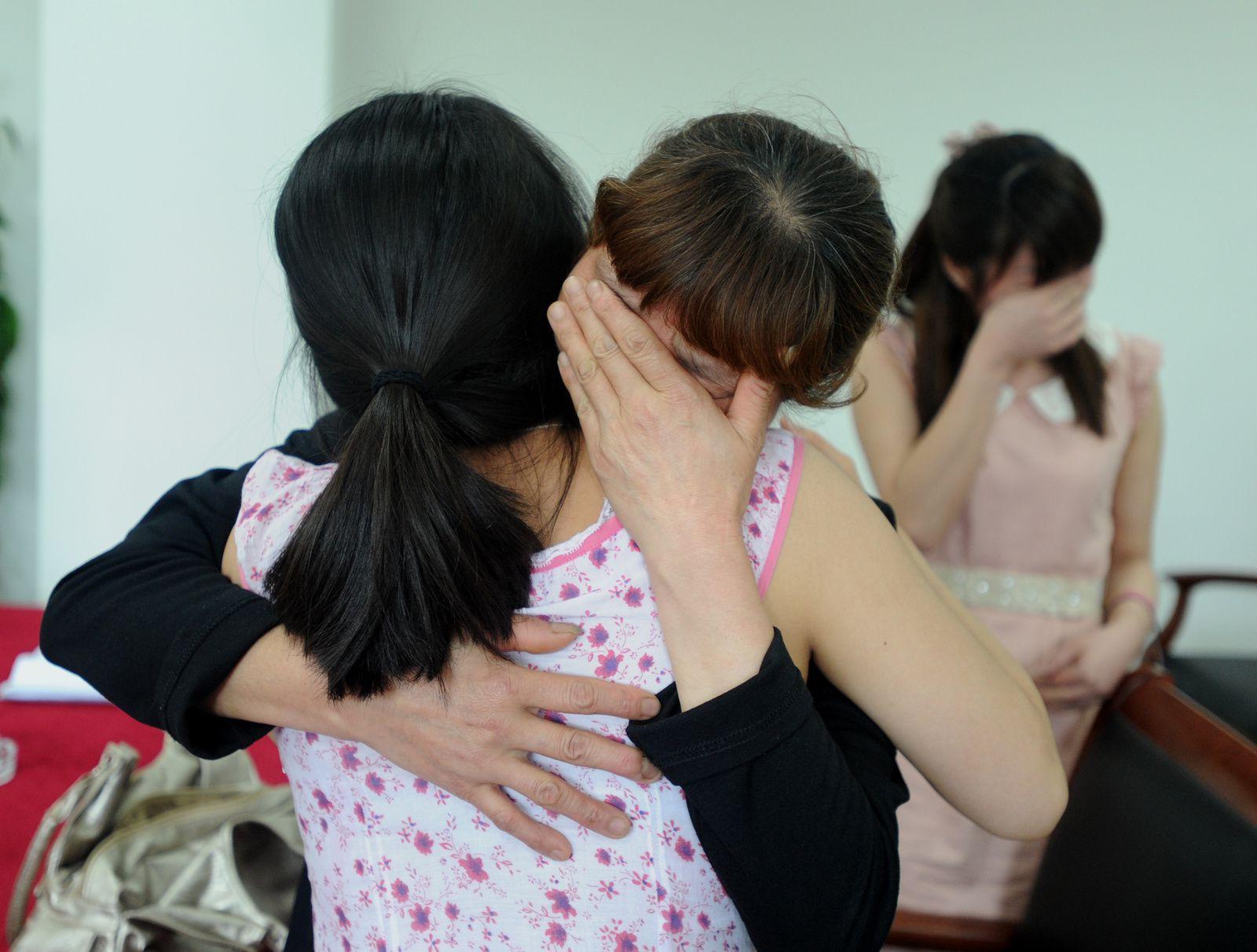 L'auteure dans les bras d'une mère. À l'arrière plan, son autre fille.