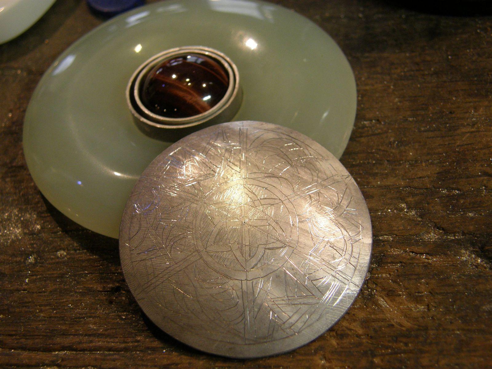 Le cabochon dans son sertis, au centre du disque et une plaque d'argent preparee pour faire le dos du bijou.