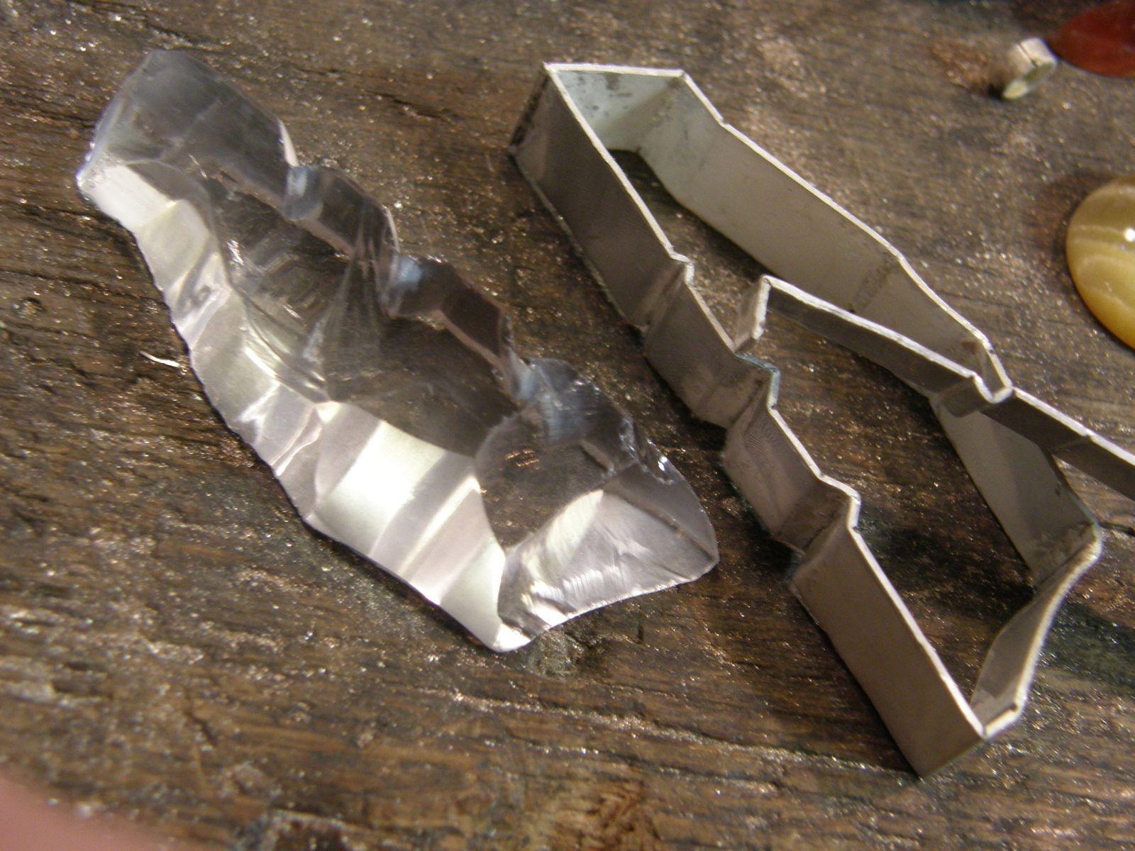 La pierre, le sertis et le soutien de la pierre dans le sertis, en cours de fabrication.