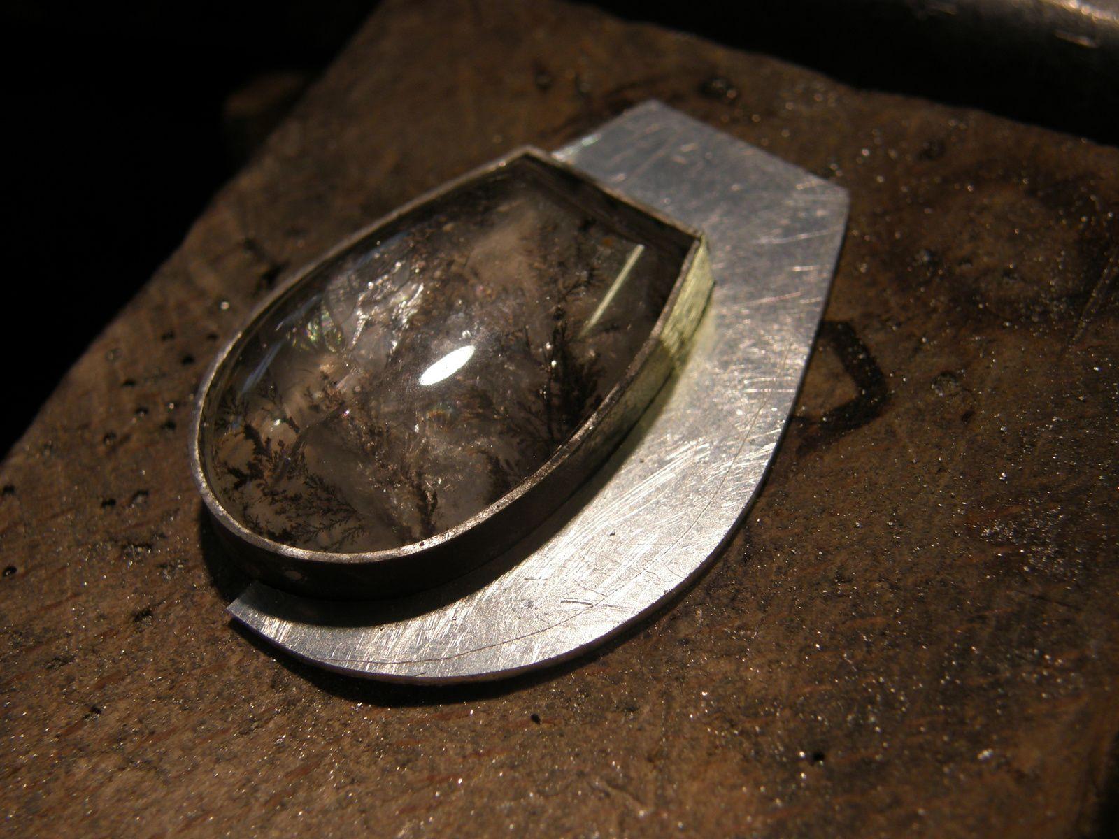 La pierre dans son serti avec le corps decoupe&#x3B; le corps est bombe&#x3B; une bate pour faire de l'epaisseur et le tube de passage de la chainette.