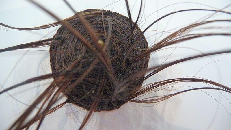 Détail d'une oeuvre d'Alice Calm faite de cheveux tressés